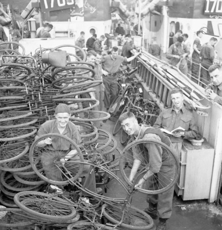 """Infantrymen checking bicycles aboard an LCI(L) of the 2nd Canadian (262nd RN) Flotilla. Southampton, England, 6 June 1944.(L-R): Privates Reg Martin and Rodney MacNeill, both of The Lorne Scots (Peel, Dufferin and Halton Regiment); Private George Banning of The Cameron Highlanders of Ottawa (M.G.). Date: 6 June 1944 Place: Southampton, England, Extent: 1 photograph ; 2 1/4 sq. in. Negative Film B/W - safety film Terms of use Credit: Lt Gilbert Alexander Milne / Canada. Dept. of National Defence / Library and Archives Canada / PA-136999Restrictions on use: NilCopyright: Expired Additional name(s) Photographer: Gilbert Alexander Milne, 1914- MLU Note: Probably June 4th (or the morning of the 5th). The LCI is still in harbour in Southampton. The rifle companies (of the NNSH so probably all) embarked on the morning of the 4th then found out about the delay. In this photo, the men have doffed their helmets and gear (and rifles it seems) probably in the bunks below deck. The LCI flotilla didn't cast off till the afternoon of the 5th, when the LCI moved down the Southampton channel. In the evening of the 5th they passed between the Isle of Wight and Portsmouth into the open sea where they would regroup. The bicycles were supposed to speed the second wave regiments to the front once they disembarked the LCI, but they were rarely if ever used. Veterans say a lot of French kids got new bikes that day. Check this photo against PA115614 -- same time. This is 262-276 (#1705-""""Lucky"""" with the Cdn maple leaf that says """"Canada"""".) 1705 was a mixed loading carrying members of the Highland Light Infantry of Canada, Stormont Dundas Glengarrian Highlanders, the Defence and Employment Platoon of 9 Brigade Headquarters and members of the Canadian Provost Corp. In Southampton on June 5th the sun sets at 9:14pm. Official photo caption suggests two men are from Lorne Scots, but that regiment was Defence Regt for 1st Corps in Italy, so that must be incorrect. Not sure who they"""